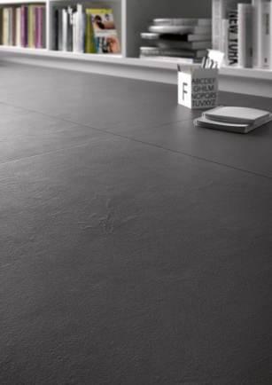 Cerámica en despacho en el suelo son piezas grandes en tono gris antracita. Dos pequeños objetos blancos que destacan.