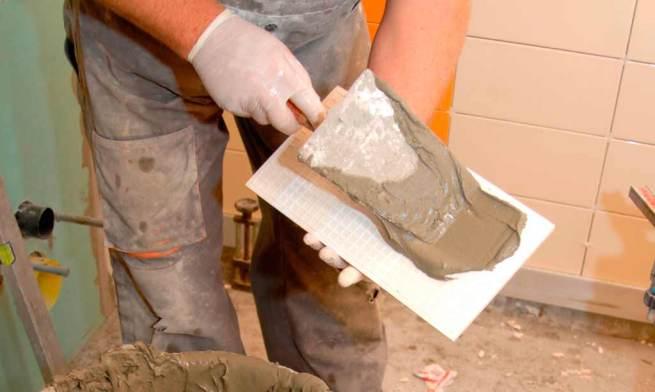 Reformar cuarto baño plano corto de un obrero colocando cemento en un azulejo del cuarto de baño.