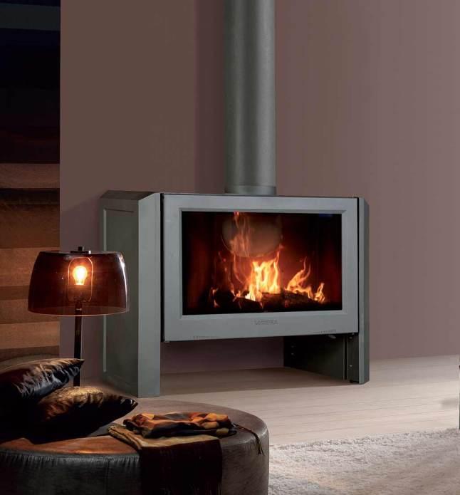Chimeneas y estufas donde aparece la estufa de leña LEÓN de Lacuzna. Está encendida en un salón donde hay una luz tenue encendida.