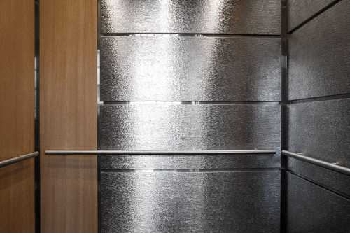 "Elevator Interior Design GR703 incorporates horizontal and vertical elevator wall panels infusing high contrast with formica ""natural cherry"" laminate and pattern stainless steel within this highly trafficked public building in Minneapolis, MN."