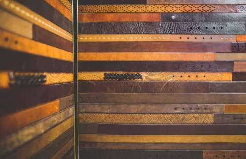 Elevator cab interior design modernization design engineered & manufactured by G&R Custom Elevtor Cabs: The bronze-edged lower elevator wall panels are made from repurposed leather belts of various size, color, wear, and texture.