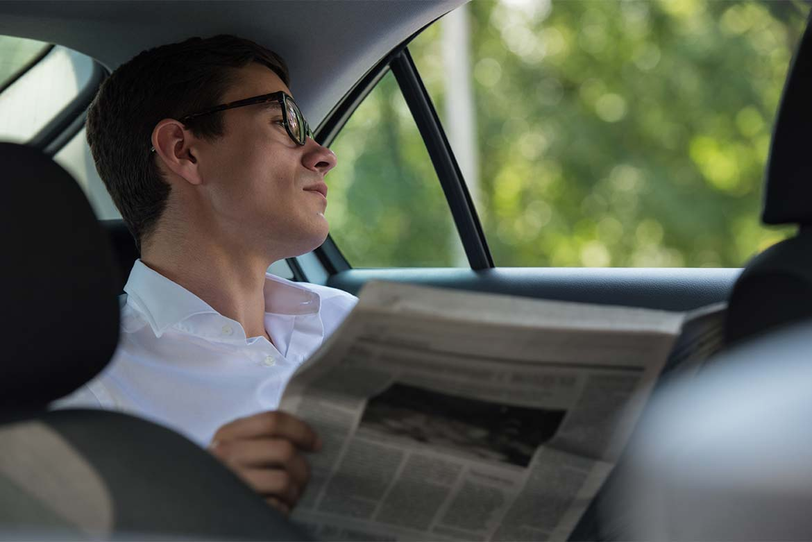 An image of a man reading a complimentary newspaper in the back of a GandT Executive car