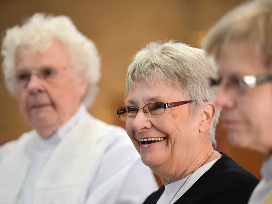 Rose Henzler, center, is studying to become a womanpriest.