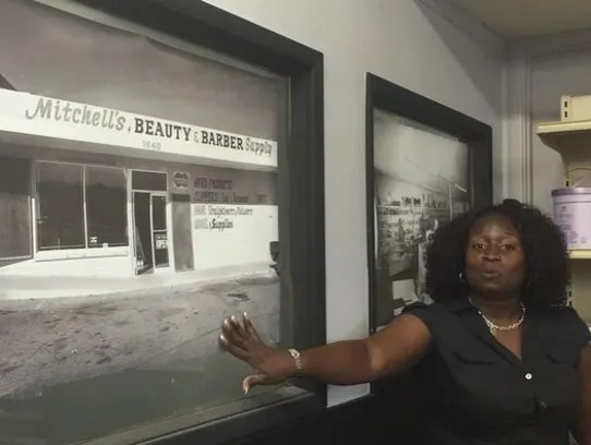 Melissa Cox stands next to a photo of the original