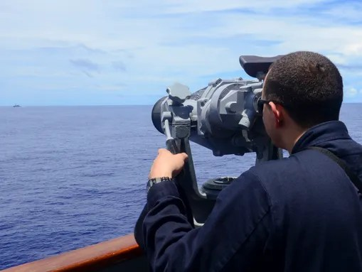 Ensign Matt Delavega uses high-powered binoculars to