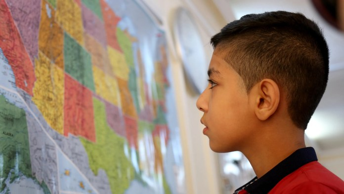 Syrian refugee Hamzeh Jouriyeh, 12, studies a map of the United States in the Amman, Jordan office of the International Organization for Migration. Jouriyeh, his three siblings and his parents were headed to San Diego, Calif, as part of a year-long program to resettle 10,000 Syrian refugees in the United States.