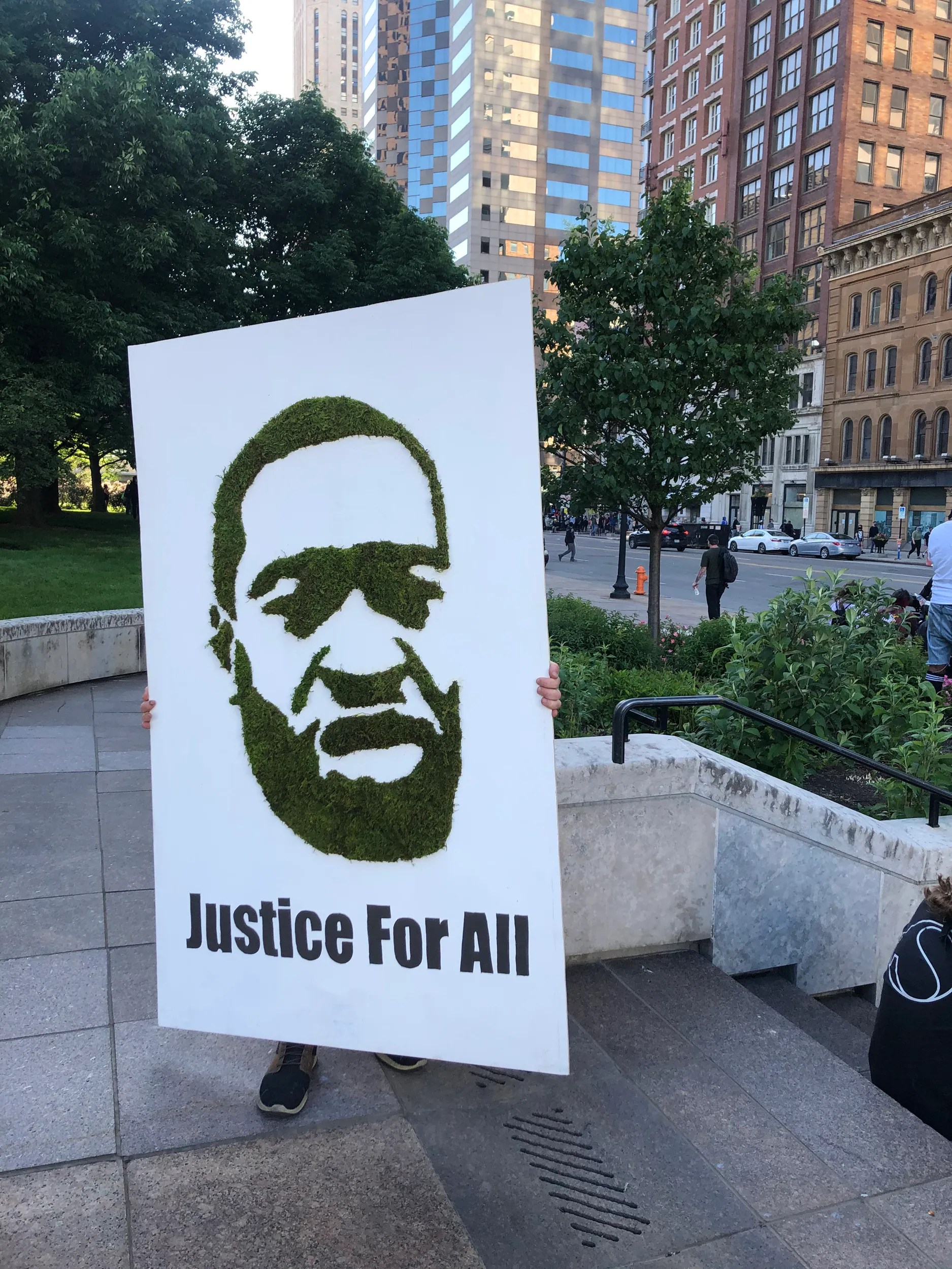 A protestor carries a poster featuring a picture of George Floyd on May 31, 2020. Floyd, a 46-year-old black man, was killed while in police custody after allegedly passing a counterfeit $20 bill at a convenience store.