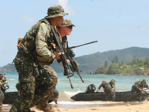A U.S. Marine and a Filipino marine secure the beach