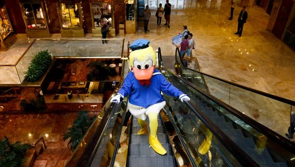 A person in a Donald Duck costume rides an escalator