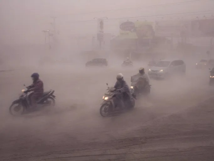 Volcanic ash swirls among motorcyclists in Yogyakarta, Indonesia on Feb. 14.