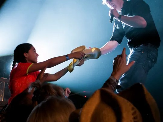 Joe Nichols reaches down to sign a hat for Michelle