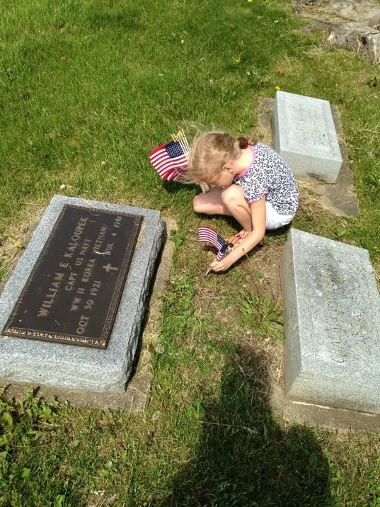 Kaanan's daughter placing flags on Memorial Day.JPG