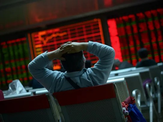 An investor looks at screens showing stock market movements