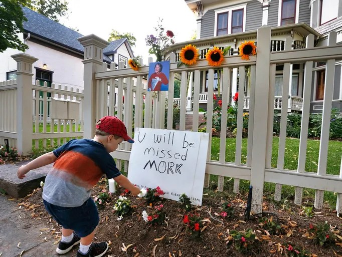 AJ Polis leaves a flower outside a home in Boulder, Colo., alongside a placard and photo of the late actor Robin Williams on Aug. 11.  Williams played Mork from Ork in the television series