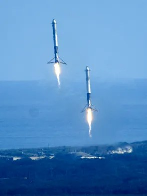 The twin boosters from SpaceX's Falcon Heavy make a