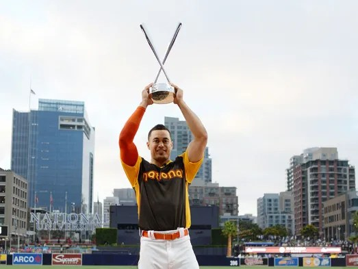 Giancarlo Stanton hoists the trophy after defeating