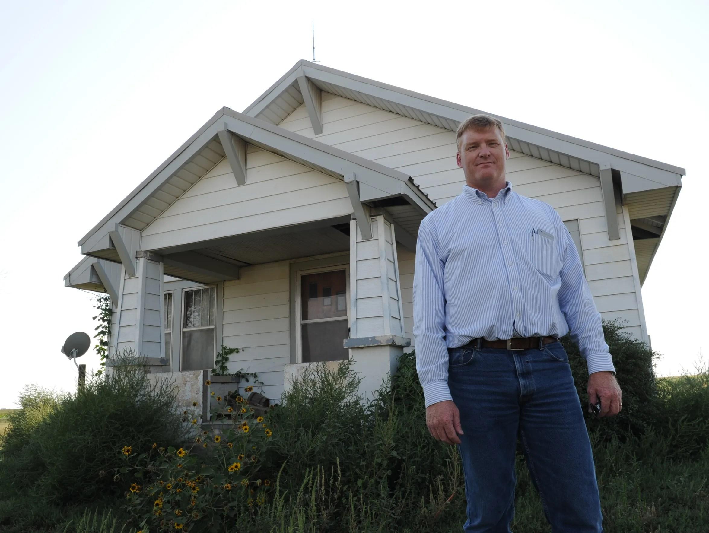 Jay Garetson stands in front of a farmhouse where he
