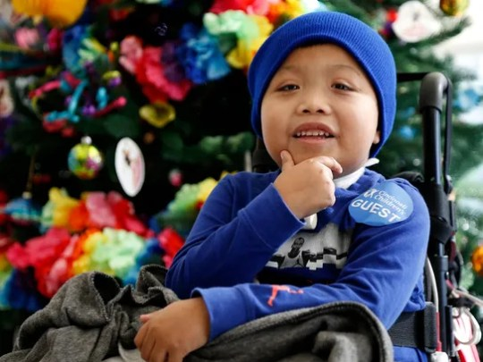 Ricky Solis, 6, smiles as his mother speaks at Cincinnati
