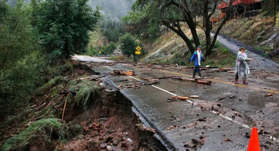 Patrick Tinsley, left, and his sister, Mary Kerns, walk along a closed road from their mountain community of Magnolia after a massive flood on Sept. 13 in Boulder Canyon, Colo.