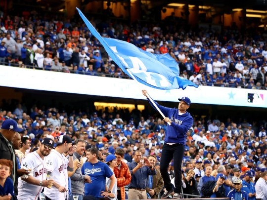 Actor Rob Lowe swings earlier with a flag of Los Angeles Dodgers