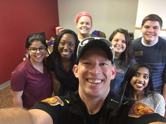 Major Russell poses for a picture with a mix of University