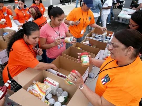 Volunteers sort through donations of food, medicine