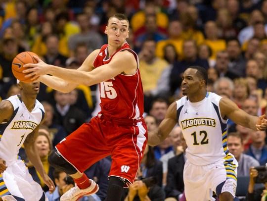In this 2014 game, Wisconsin's Sam Dekker grabs a rebound in front of Marquette's Derrick Wilson.