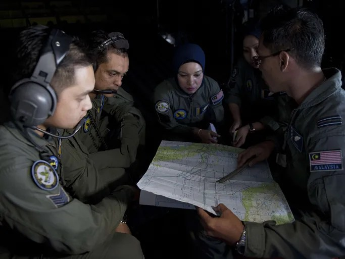 Royal Malaysian Air Force navigator Capt. Izam Fareq Hassan, right, talks with his crew members aboard a Malaysian Air Force CN235 aircraft during a search and rescue operation over the Strait of Malacca.