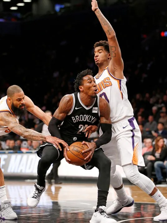 Phoenix Suns center Tyson Chandler, left, and Phoenix Suns forward Marquese Chriss (0) gang up on Brooklyn Nets forward Rondae Hollis-Jefferson (24) in the first half of an NBA basketball game, Tuesday, Oct. 31, 2017, in New York. (AP Photo/Kathy Willens)