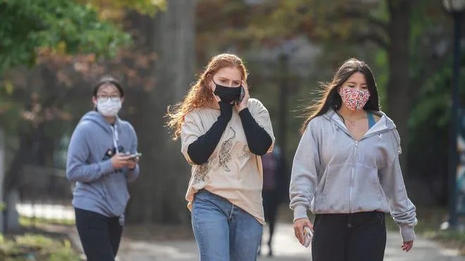 Masked University of Michigan students walk around campus in Ann Arbor Tuesday, Oct. 20, 2020 after Washtenaw County Health Department issued a Stay in Place order for University of Michigan undergrad students due to the rising number of COVID-19 cases on campus. Photo by Ryan Garza, Detroit Free Press