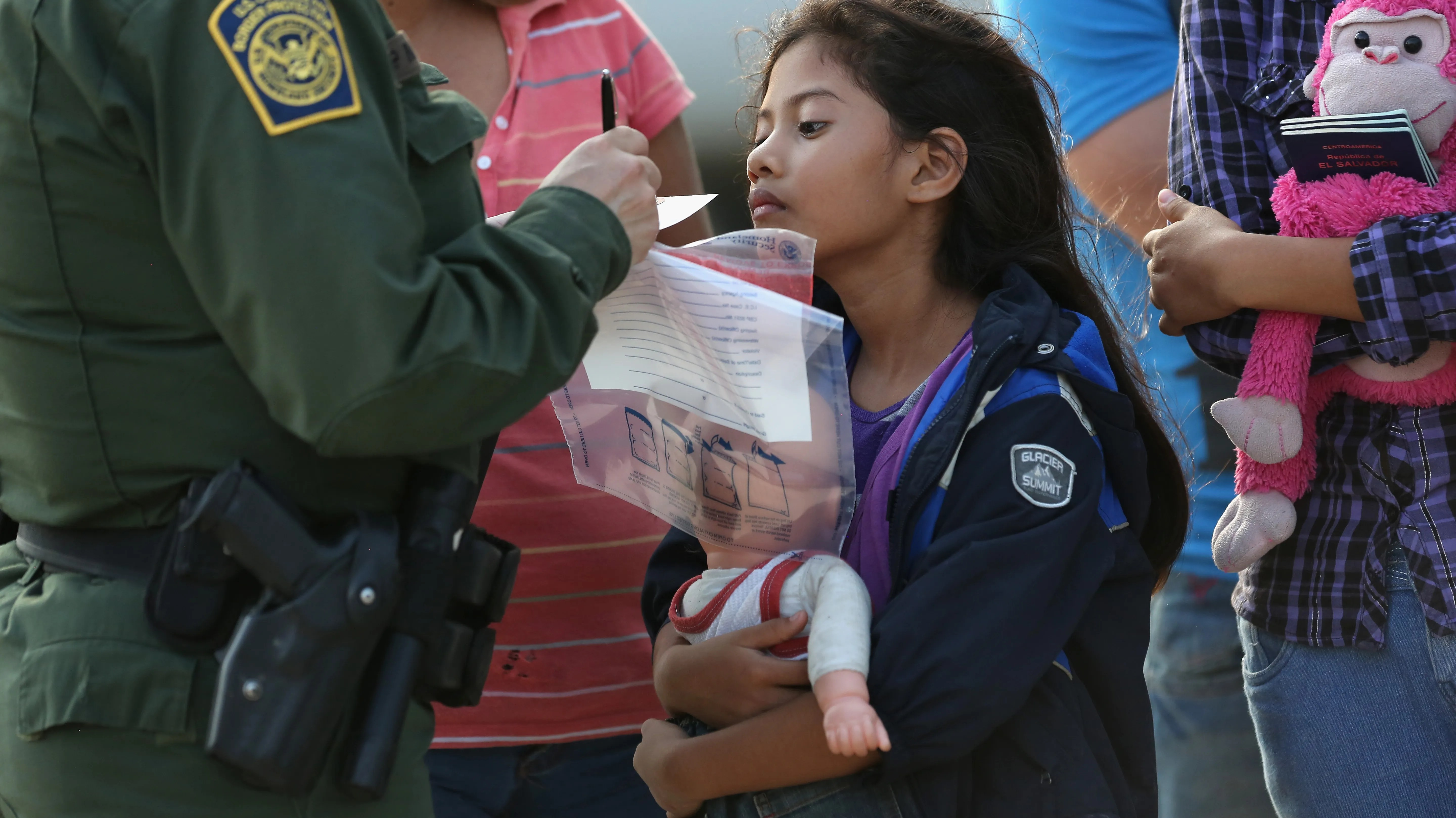 Salvadoran immigrant Stefany Marjorie, 8, watches as a U.S. Border Patrol agent records family information July 24 in Mission, Texas. Tens of thousands of families and unaccompanied minors from Central America have crossed illegally into the USA this year.