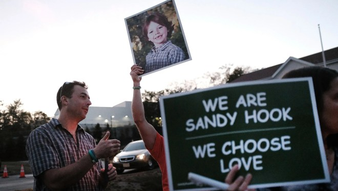 Mark Barden holds up a picture of his son Daniel who was killed in the Sandy Hook massacre during a vigil on October 4, 2017 in Newtown, Connecticut.