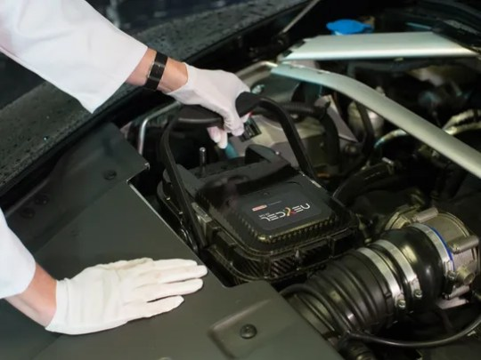 A Castrol technician places the Nexcel system into