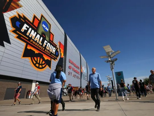 Basketball fans walk by outside of University of Phoenix