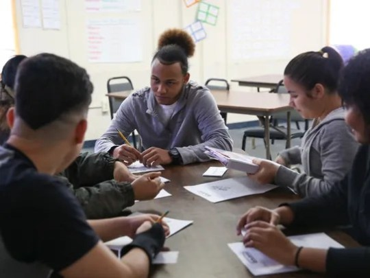 Misael Delgado, 17, works in a group during class at