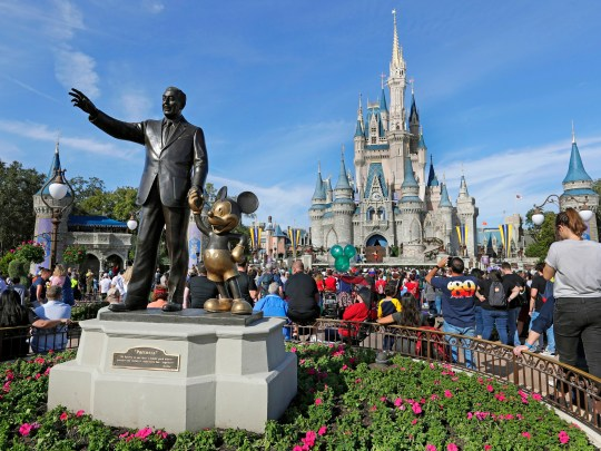 Guests watch a show near a statue of Walt Disney and Micky Mouse in front of the Cinderella Castle at the Magic Kingdom at Walt Disney World in January 2019.