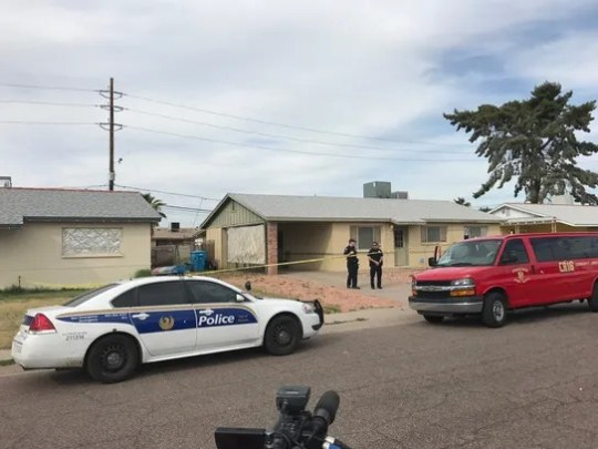 Police gather outside a north Phoenix home where a