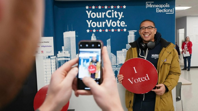 Jared Mollenkof has his photo taken after voting at the Minneapolis Early Voting Center on Friday. Mollenkof and Davis Senseman arrived the night before so they could be among the first voters in the 2020 election when the center opened at 8 a.m.