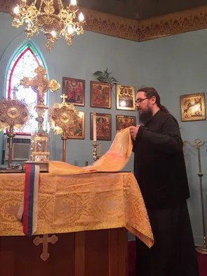 Father Borjan Vitanov arranges a cloth on the pulpit