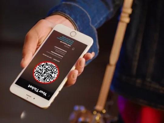 Man holding smartphone displaying AMC Stubs A-List app