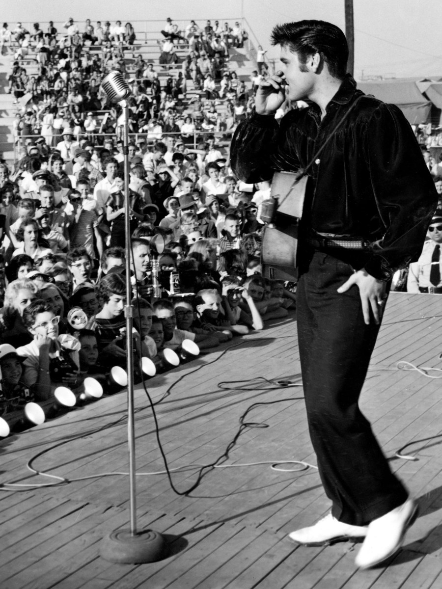 Elvis Presley is singing in one of two grandstand shows at the Mississippi-Alabama Sate Fair Aug. 26, 1956. The young star causes a near riot with his singing in Tupelo, Miss., where he was born.