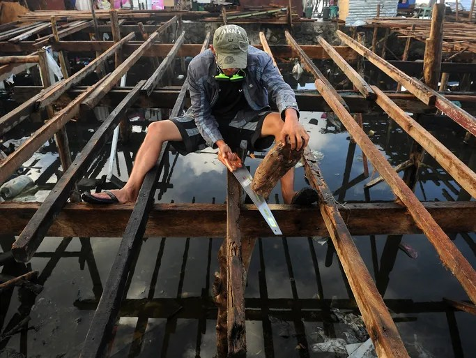 A man rebuilds his home which was destroyed by Typhoon Haiyan on a bay on Nov. 27 in Tacloban, Philippines.