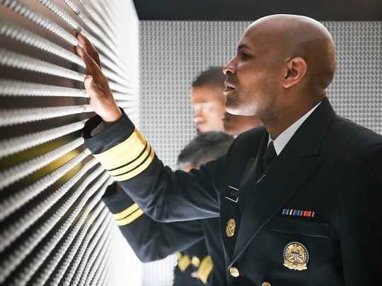 "Surgeon General Jerome Adams touching ""The Pill Wall"""
