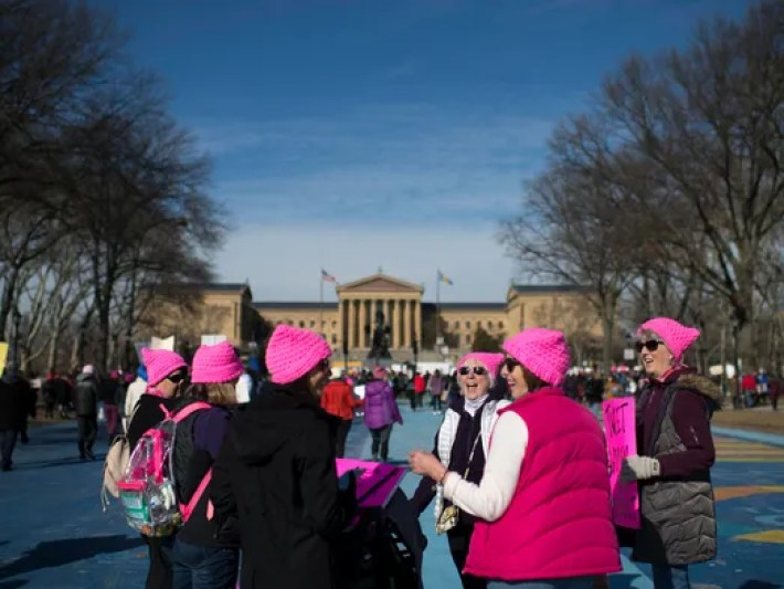A group of women wearing pink hats gather in front
