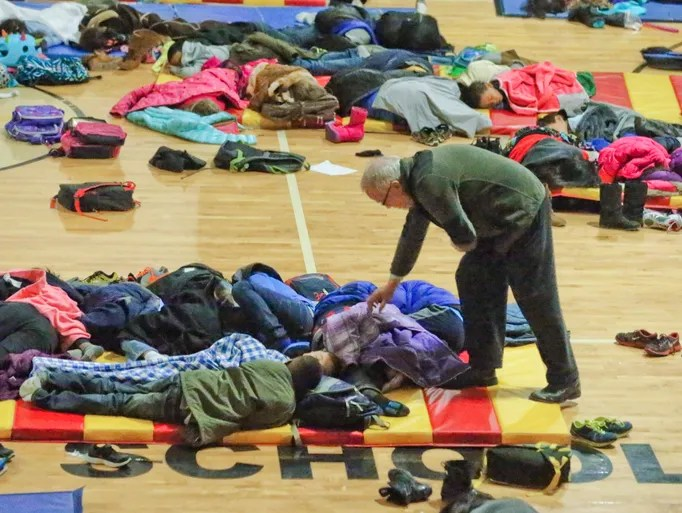 A teacher at E. Rivers Elementary school covers sleeping children in the gymnasium. The kids were forced to stay in the aftermath of a winter storm in Atlanta.