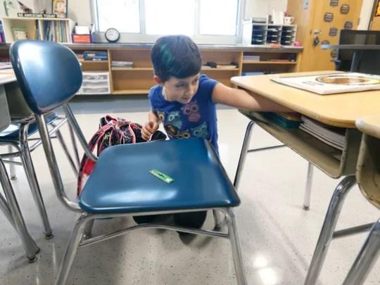 Gwen Giardina, 9, organizes her desk while taking a