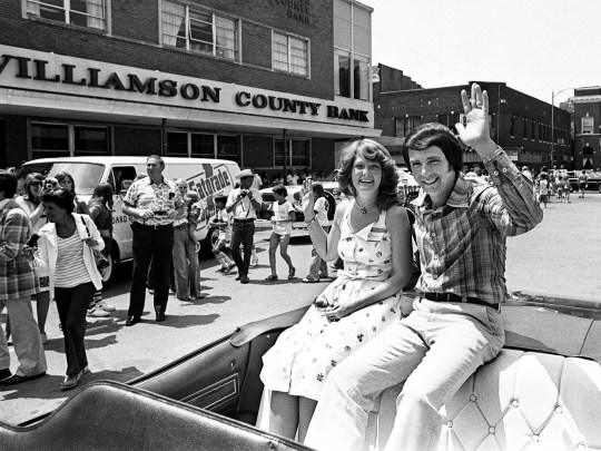 Darrell Waltrip and his wife Stevie wave to the crowd in downtown Franklin, Tennessee, on July 13, 1977, as they arrive for Darrell Waltrip Day festivities.