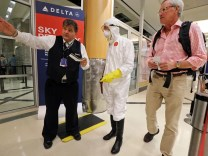Two days after a man in Texas was diagnosed with Ebola, Dr. Gil Mobley, a Missouri doctor, checks in to board a plane dressed in full protection gear Thursday morning, Oct. 2, 2014, at Hartsfield-Jackson Atlanta International Airport. He was protesting what he called mismanagement of the crisis by the federal Centers for Disease Control and Prevention. (AP Photo/Atlanta Journal-Constitution, John Spink) MARIETTA DAILY OUT; GWINNETT DAILY POST OUT; LOCAL TELEVISION OUT; WXIA-TV OUT; WGCL-TV OUT