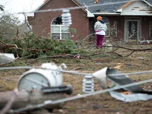 A woman walks her dogs through debris in a neighborhood