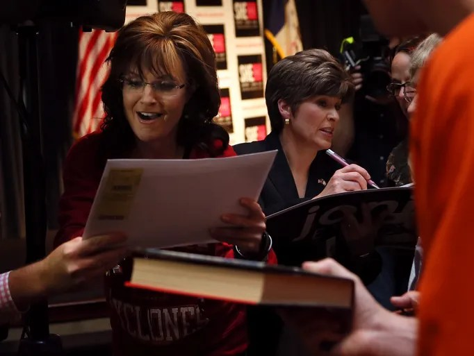 "Sarah Palin signs autographs beside Joni Ernst following the ShePAC ""Heels On, Gloves Off!"" rally to campaign for Joni Ernst, who is running for the U.S. Senate at the West Des Moines Hy-Vee Conference Center Sunday, April 27, 2014."